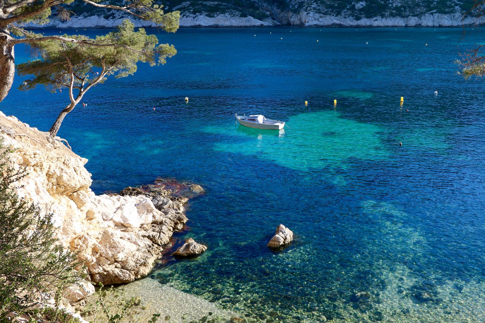 Calanques et bateau à la dérive sur une mer turquoise